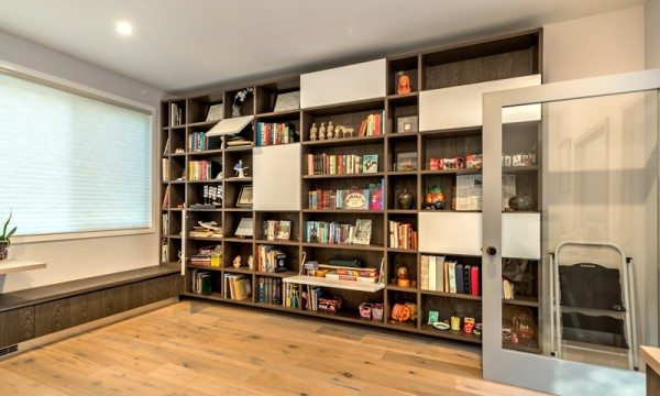 The expansive library and home office features a wall of shelves with cabinet doors interspersed throughout.