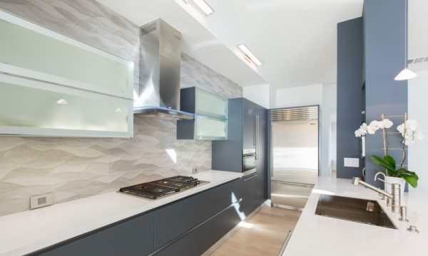 This modern kitchen features cabinets from Aran Cucine: Lower cabinets from the Erika collection in Slate Gray; white frosted glass upper cabinets from the Volare collection.