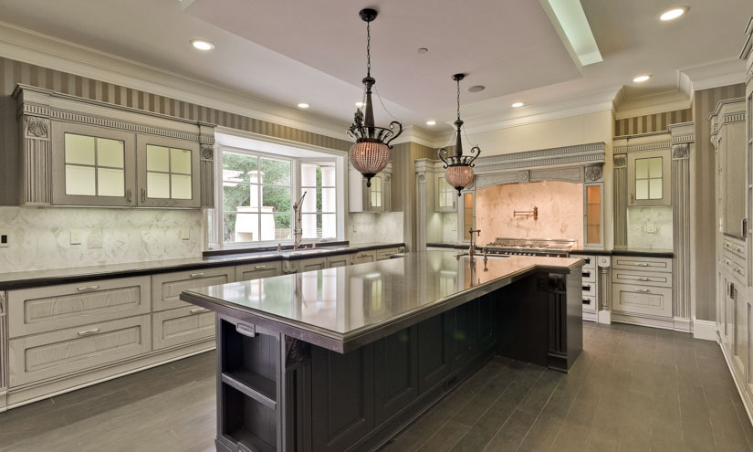 This traditional kitchen uses multiple layers of lighting: Recessed cans and up lighting over the island for ambient light; under cabinet lighting and task lighting over the gas range; pendants over the island for ambiance; decorative in-cabinet lights; and large windows for natural light.