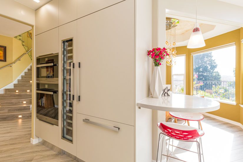 Kitchen island with built-in appliances and built-in breakfast high-top table.