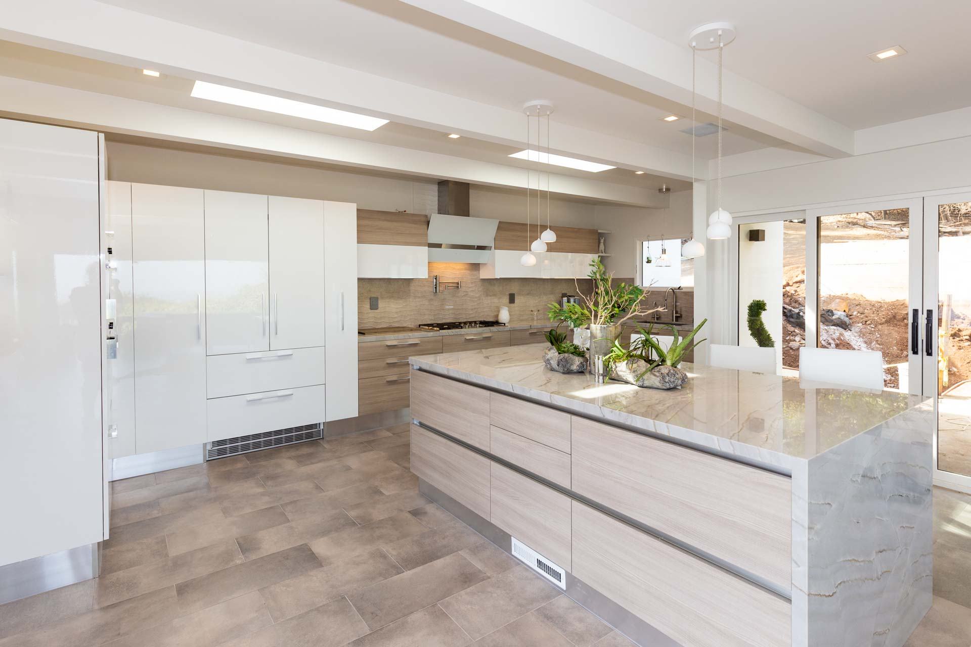 Beige and white kitchen with impressive greenery on island