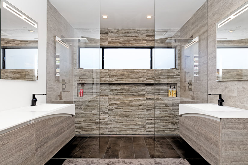 Master bathroom in modern design with two vanities and a large walk-in shower