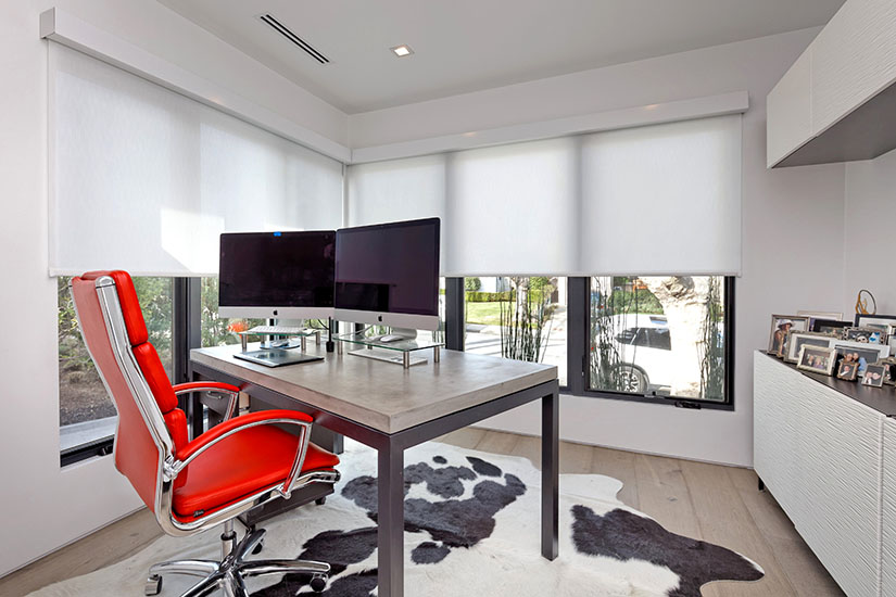 Home office with large windows and red chair reflecting modern house design