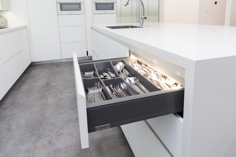 White kitchen cabinet drawer with interior lighting.