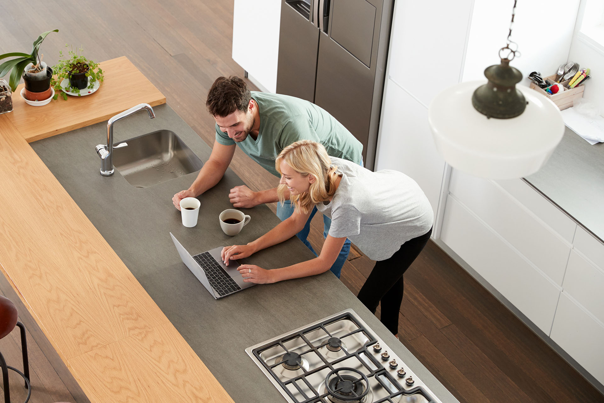 Man and woman looking at laptop in modern kitchen